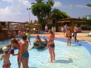 Actividades y diversión en la piscina infantil con los toboganes, cascadas de agua, pueden montarse y jugar con el tiburón, el hipopotamo