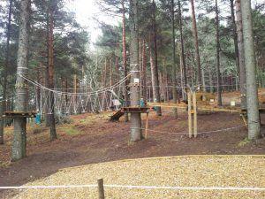 parque de aventuras con arboles altos, mucha vegetación, retos, deporte al aire libre